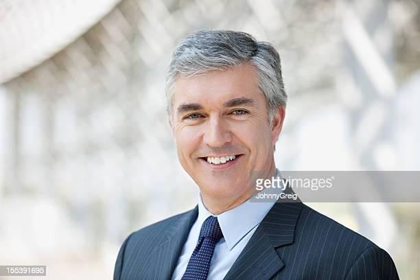 Photo of a mature businessman smiling for a posed head shot