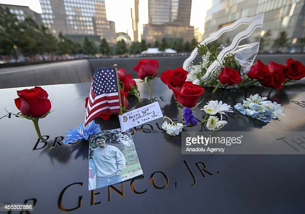 A photo of a victim of 9/11 terrorist attacks and red roses are seen on the September 11 memorial in New York United States on September 11 2014...