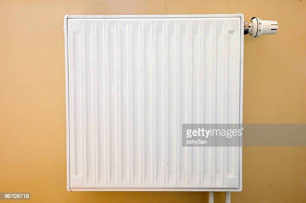 A photo of a white radiator attached to a brown painted wall