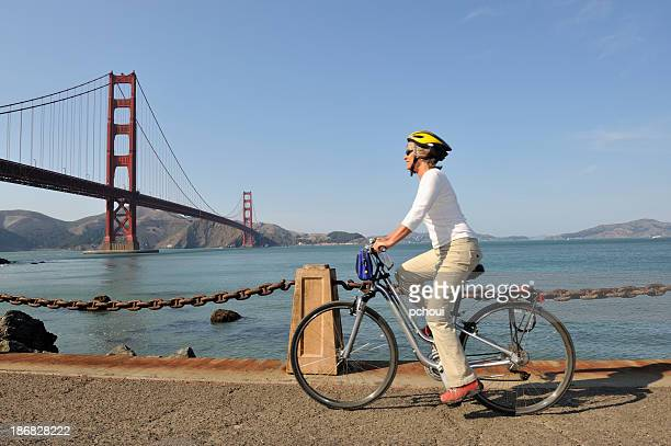 A photo of a woman cycling near the Golden Gate Bridge
