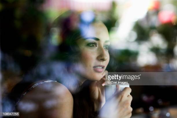 Photo of a woman drinking coffee through a window