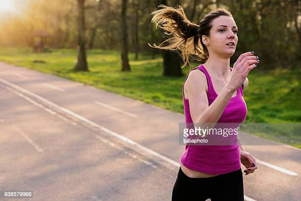 Photo of a woman running while sun is setting