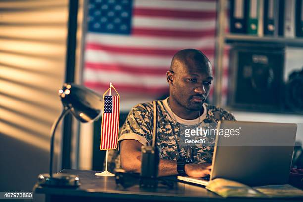 Photo of a young african american soldier using his laptop