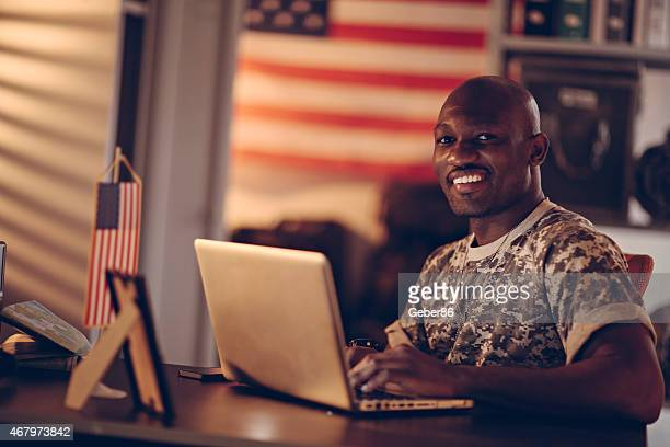 Photo of a young african american soldier using laptop