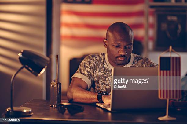 Photo of a young american soldier with laptop