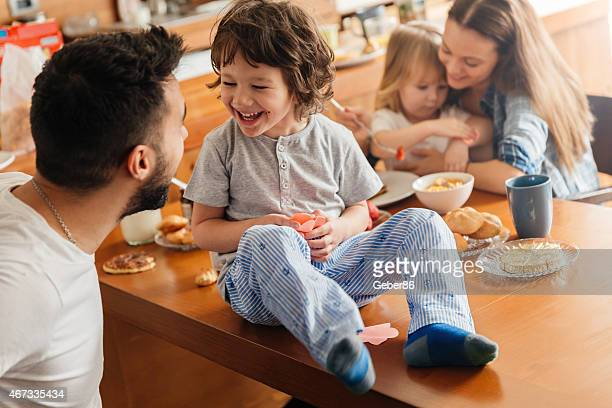 Photo of a young and playful family having breakfast