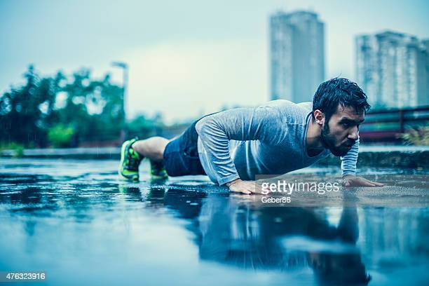 Photo of a young athletic man exercising in the rain