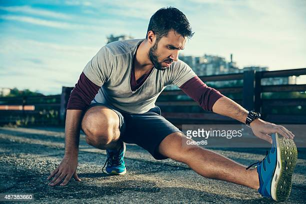 Photo of a young athletic man stretching