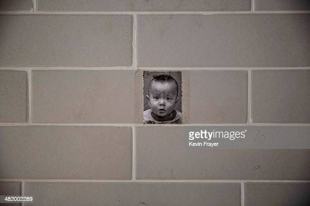 A photo of a young Chinese orphaned boy hangs on the wall at a foster care center on April 2 2014 in Beijing China China's orphanages and foster...