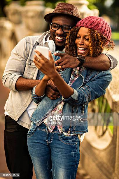 Photo of a young happy african american couple with smartphone