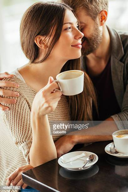 Photo of a young happy couple enjoying in cafe together