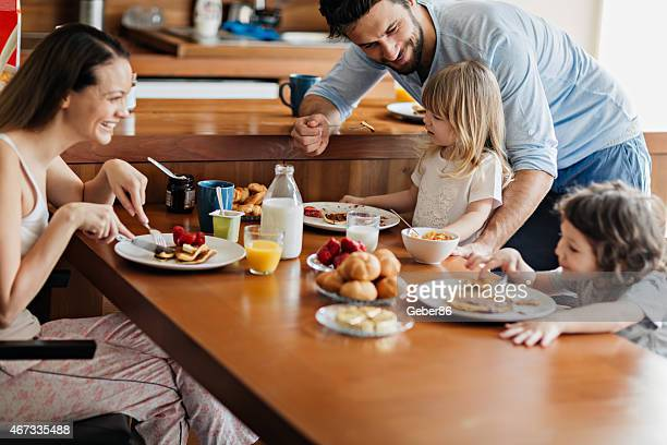 Photo of a young happy family having pancake breakfast