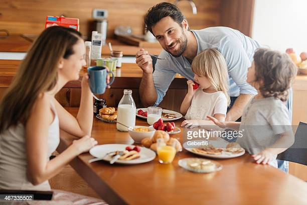 Photo of a young happy family having their breakfast