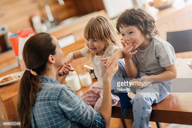 Photo of a young mother and her children having breakfast