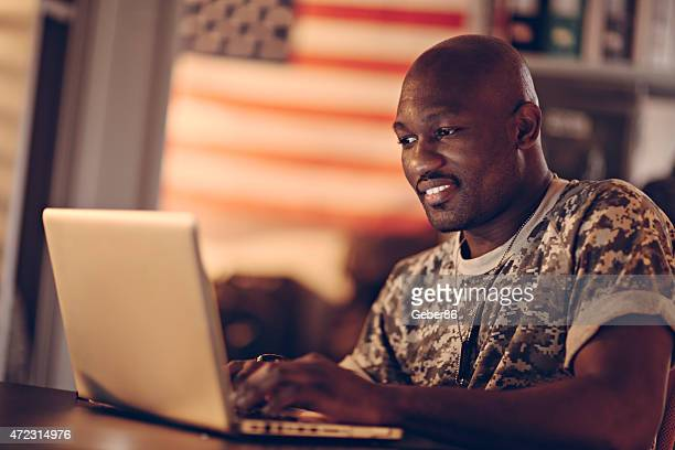 Photo of a young smiling soldier with laptop