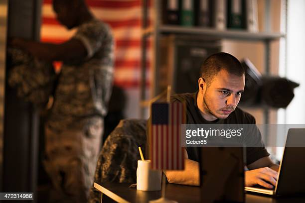 Photo of a young soldier bu his laptop