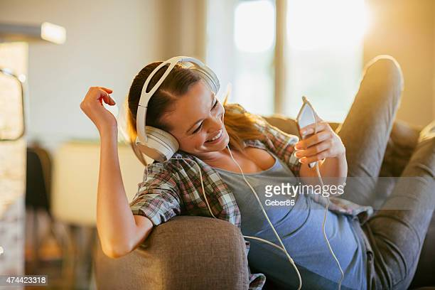 Photo of a young woman in sofa listening to music