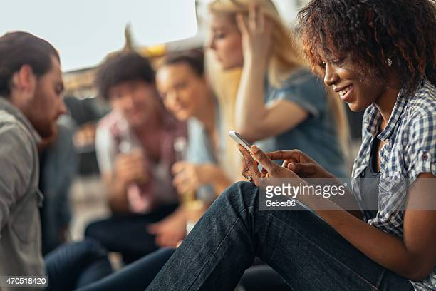 Photo of a young woman using smartphone while with friends