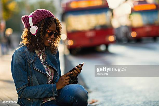 Photo of a young woman with headphones and smartphone