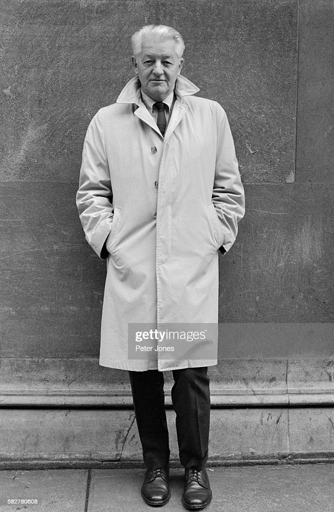 Photo of American author Wallace Stegner This full length photo shows Stegner standing on a sidewalk with his hands in his coat pockets Undated...