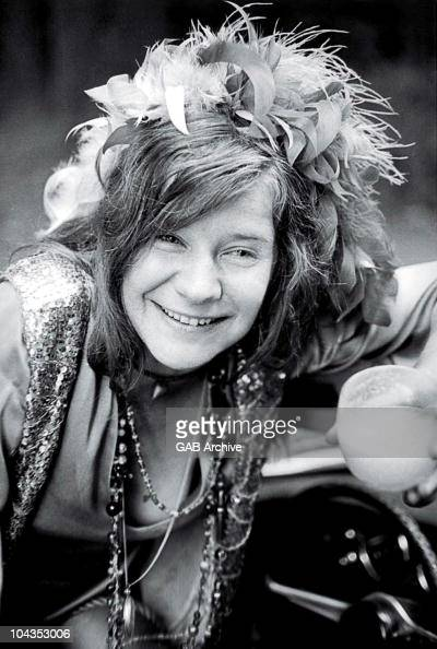 Photo of American singer Janis Joplin holding a glass in a car