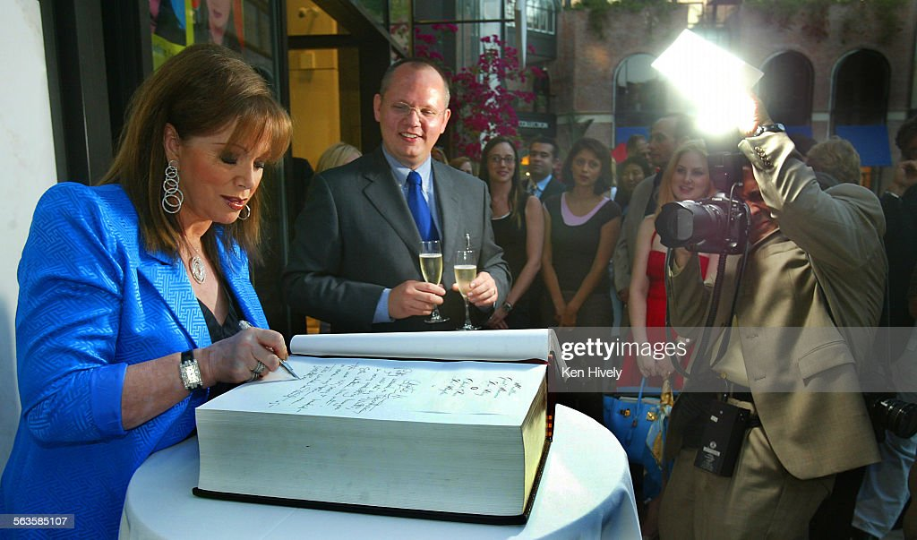 Photo of Author Jackie Collins writing in her entry in book as Montblanc CEO North America looks on with guest Montblanc is sponsoring a giant...