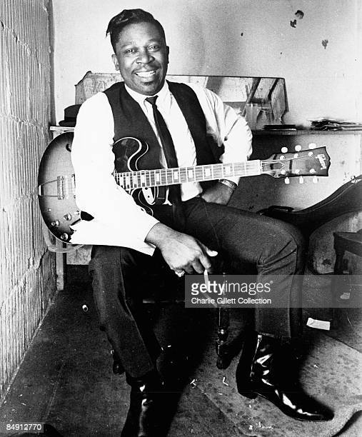 Photo of BB KING Posed Sitting with guitar and cigarette