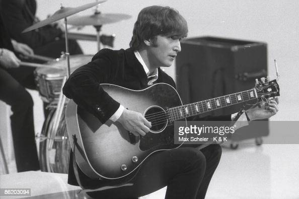Photo of BEATLES and John LENNON of the Beatles tuning guitar during the filming of 'A Hard Day's Night' at the Scala Theatre