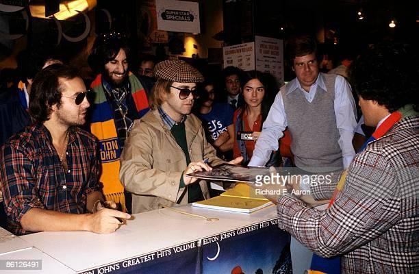 Photo of Bernie TAUPIN and Elton JOHN Bernie Taupin Elton John signing copies of Elton John's Greatest Hits Volume II