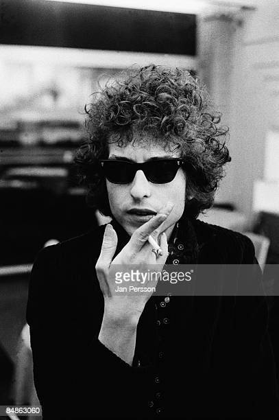 Photo of Bob DYLAN posed looking to camera wearing sunglases holding cigarette
