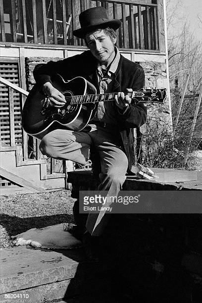 WOODSTOCK Photo of Bob DYLAN posed playing acoustic guitar outside Byrdcliff home