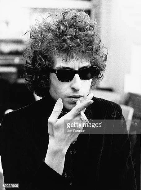 Photo of Bob DYLAN posed wearing sunglasses holding cigarette
