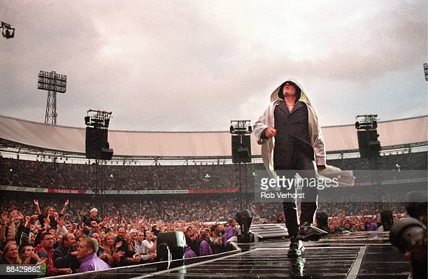 ROTTERDAM Photo of BONO and U2 Bono performing live on stage at the Feyenoord Stadium during the PopMart tour showing stadium and crowds behind
