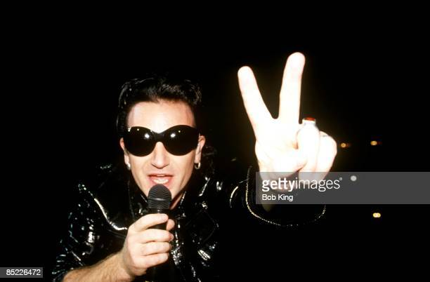 Photo of BONO and U2 Bono performing live onstage at the Aussie Stadium on the Zoo TV tour Zoomerang leg wearing sunglasses doing peace sign looking...