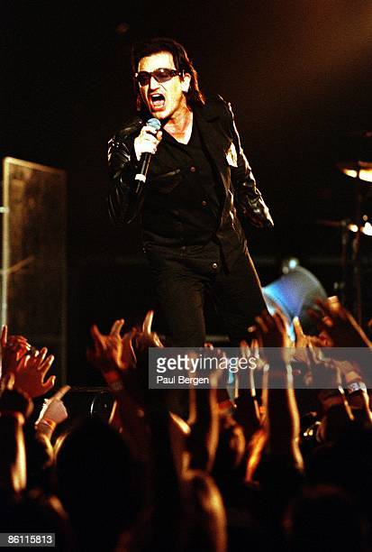 Photo of BONO and U2 Bono performing live onstage on the 1st date of Elevation tour audience hands reaching up fans
