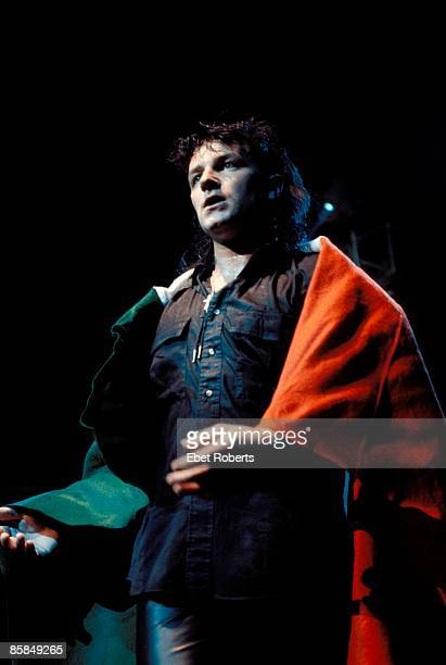 Photo of BONO and U2 Bono performing live onstage on The Unforgettable Fire tour wrapped in Irish flag