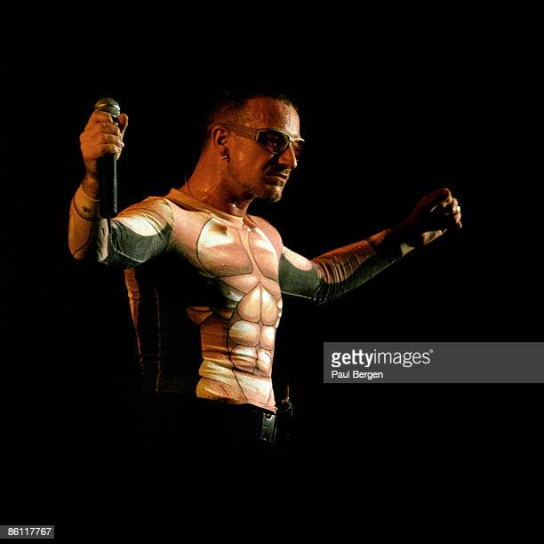 Photo of BONO and U2 Bono performing live onstage on the first date of the PopMart Tour wearing muscle print tshirt