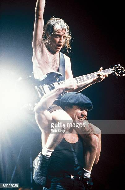 Photo of Brian JOHNSON and AC/DC and Angus YOUNG and AC DC Angus Young sitting on Brian Johnson's shoulders performing live onstage