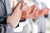 Photo of business partners hands applauding at meeting.