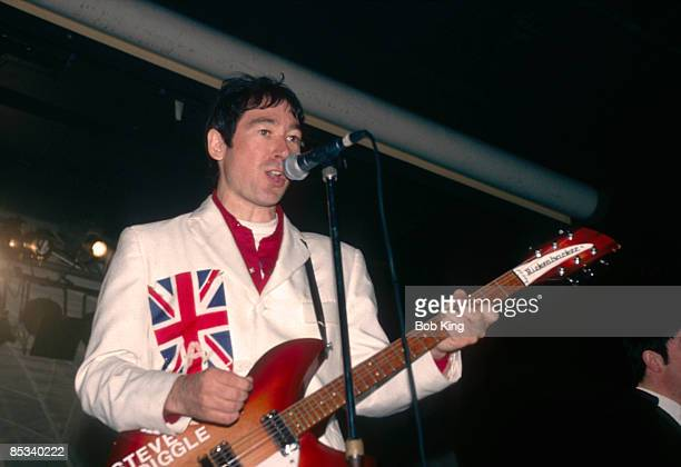 Photo of BUZZCOCKS and Steve DIGGLE Steve Diggle performing on stage Union Jack suit