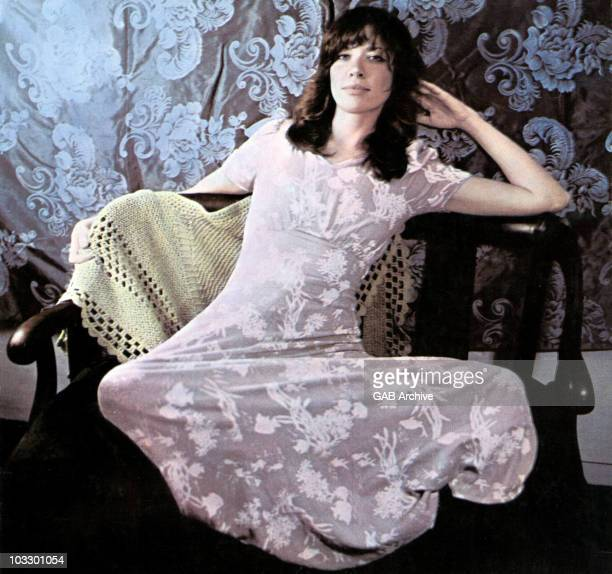 Photo of Carly Simon posed on a chair circa 1971