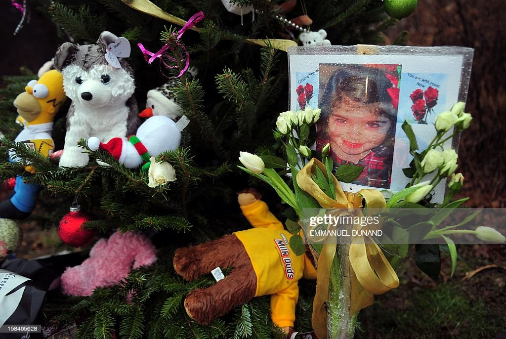 A photo of Caroline Previdi, one of the victim from an elementary school shooting is set up at a makeshift shrine to the victims of an elementary school shooting in Newtown, Connecticut, December 17, 2012. Funerals began Monday in the little Connecticut town of Newtown after the school massacre that took the lives of 20 small children and six staff, triggering new momentum for a change to America's gun culture. The first burials, held under raw, wet skies, were for two six-year-old boys who were among those shot in Sandy Hook Elementary School. On Tuesday, the first of the girls, also aged six, was due to be laid to rest. There were no Monday classes at all across Newtown, and the blood-soaked elementary school was to remain a closed crime scene indefinitely, authorities said. AFP PHOTO/Emmanuel DUNAND