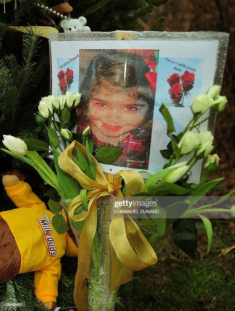 A photo of Caroline Previdi, one of the victims of the December 14, 2012 elementary school shooting, is set up at a makeshift shrine to the victims in Newtown, Connecticut, December 17, 2012. Funerals began Monday in the little Connecticut town of Newtown after the school massacre that took the lives of 20 small children and six staff, triggering new momentum for a change to America's gun culture. The first burials, held under raw, wet skies, were for two six-year-old boys who were among those shot in Sandy Hook Elementary School. On Tuesday, the first of the girls, also aged six, was due to be laid to rest. There were no Monday classes at all across Newtown, and the blood-soaked elementary school was to remain a closed crime scene indefinitely, authorities said. AFP PHOTO/Emmanuel DUNAND