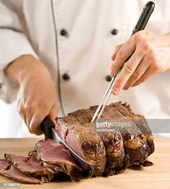 Photo of chef carving roast meat