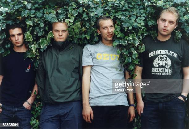 Photo of Chris MARTIN and COLDPLAY and Jonny BUCKLAND and Will CHAMPION and Guy BERRYMAN Posed group portrait in hedge LR Guy Berryman Will Champion...