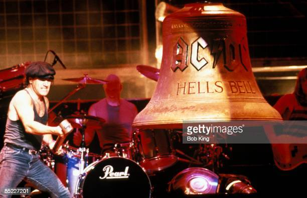 CENTRE Photo of Chris SLADE and Brian JOHNSON and AC/DC and AC DC Brian Johnson with hammer banging 'Hells Bells' bell with Chris Slade behind on...