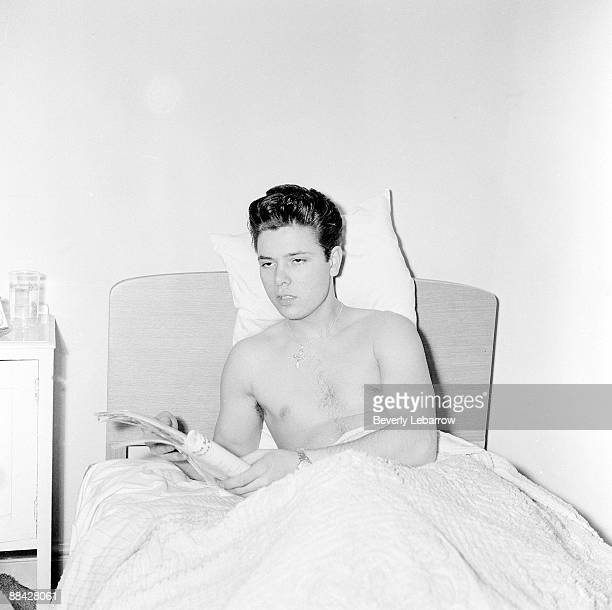 Photo of Cliff RICHARD posed lying in bed reading c1958/1959