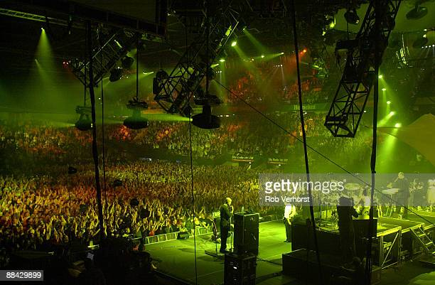 AHOY Photo of CONCERT and STAGE and VENUES Arena concert venue showing band on stage lighting rigs crowds cheering