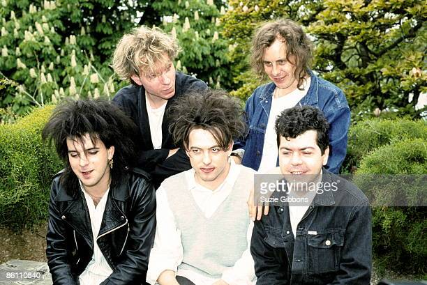 FESTIVAL Photo of CURE and Simon GALLUP and Boris WILLIAMS and Robert SMITH and Porl THOMPSON and Lol TOLHURST Posed group portrait LR Simon Gallup...