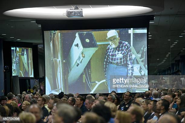 A photo of discoverer of Pluto Clyde Tombaugh is shown as people wait for telemetry from the New Horizons probe at the Johns Hopkins University...
